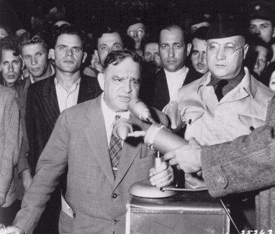 L'ancien maire de New-York Fiorello H. La Guardia, lors d'une visite des camps de l'UNRRA (Administration des Nations Unies pour les secours et la reconstruction) en Europe, parle à des survivants. Camp de personnes déplacées de Duppel. Allemagne, 20 août 1946.