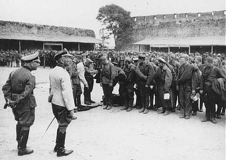 Soviet prisoners of war interrogated by German soldiers upon arrival at a prison camp. Lida, Poland, 1941.