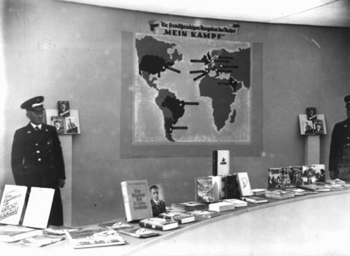 Exibição de publicações nazistas — com os títulos anti-semitas cuidadosamente disfarçados – em exposição durante as Olimpíadas de Berlim. O cartaz na parede mostra os países onde o livro de Hitler, <i>Mein Kampf</i> (Minha Luta) havia sido traduzido para as línguas nativas. Berlim, Alemanha, agosto de 1936.