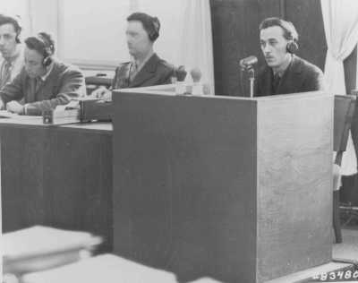 A Polish former inmate of Auschwitz identifies Oswald Pohl while on the stand for the prosecution during the Pohl/WVHA trial. This took place in a room in the Palace of Justice which was not the main courtroom. April 18, 1947.