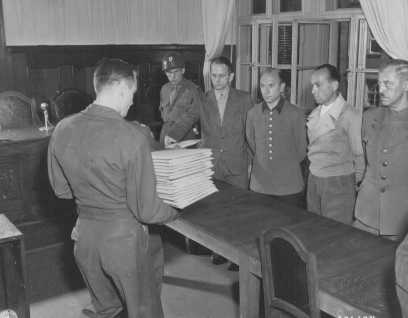 Defendant Otto Ohlendorf (second from left) receives his indictment from Colonel C.W. Mays, marshal of the Military Tribunal, before the Einsatzgruppen Trial. The other pictured defendants (left to right) are Heinz Jost, Erich Naumann, and Erwin Schulz. July 7, 1947.