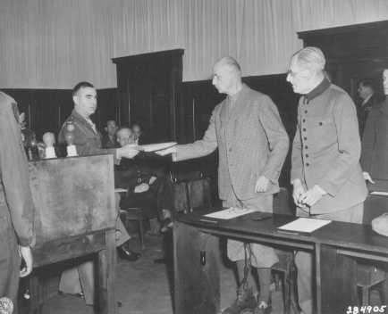 An American soldier serves former German Field Marshal Wilhelm List with his indictment at the beginning of the Hostage Case. May 12, 1947.