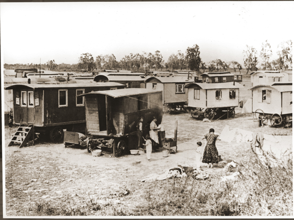 Romani (Gypsy) women boil laundry and hang it to dry in the middle of the caravan camp at Marzahn. Germany, June 1936.