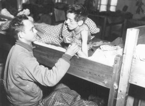 Un officier médical de l'armée américaine prend le pouls d'une femme qui survécut à une marche de la mort au cours de laquelle elle avait été forcée de marcher près de 540 km d'Asch à Volary. Volary, Tchécoslovaquie, 8 mai 1945.