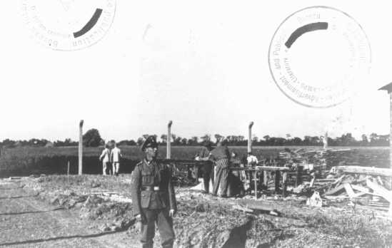 An SS guard watches prisoner laborers at construction work. Neuengamme concentration camp, Germany, wartime.