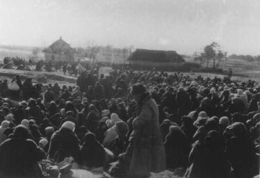 "Over one thousand Jews from the Ukrainian town of Lubny, ordered to assemble for ""resettlement,"" in an open field before they were massacred by Einsatzgruppen. Lubny, Soviet Union, October 16, 1941."