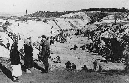 Un membre d'un Einsatzgruppe (unité mobile d'extermination) parle avec deux femmes non identifiées au sommet du ravin de Babi Yar où 33 000 Juifs furent massacrés les 29 et 30 septembre 1941. Des prisonniers de guerre soviétiques dans le ravin nivellent la terre sur le charnier. On avait fait sauter les parois du ravin à la dynamite. Kiev, Union soviétique, automne 1941.