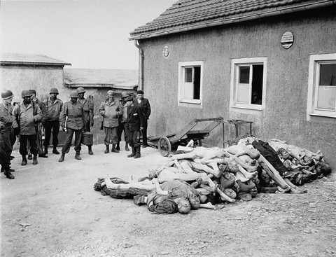 American troops, including African American soldiers from the Headquarters and Service Company of the 183rd Engineer Combat Battalion, 8th Corps, US 3rd Army, view corpses stacked behind the crematorium during an inspection tour of the Buchenwald concentration camp. Among those pictured is Leon Bass (the soldier third from left). Buchenwald, Germany, April 17, 1945.