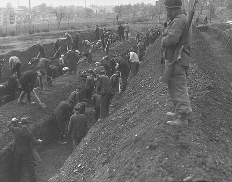 Under the supervision of an American soldier, German civilians dig mass graves for the victims of the Dora-Mittelbau concentration camp after liberation. Near Nordhausen, Germany, April 15, 1945.