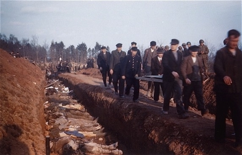 German civilians from the town of Nordhausen carry the bodies of prisoners found in the Nordhausen concentration camp to mass graves for burial. Nordhausen, Germany, April 13-14, 1945.