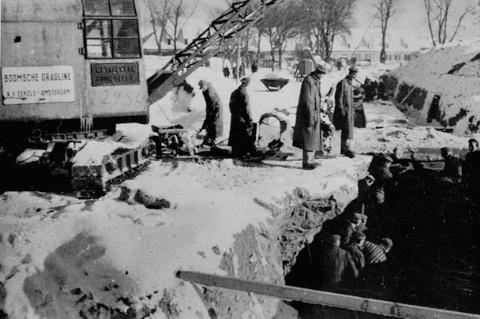Para tahanan tengah melakukan kerja paksa menggali drainase atau saluran pembuangan air di Auschwitz. Auschwitz, Polandia, 1942-1943.
