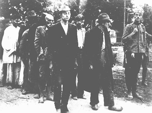 A Serbian gendarme serving the Serbian puppet government led by Milan Nedia escorts a group of Roma (Gypsies) to their execution. Yugoslavia, ca. 1941-1943.