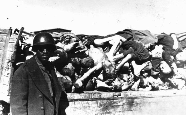 An American soldier on an inspection tour of Buchenwald poses for a photograph beside a wagon laden with corpses. The soldier is probably a member of the Headquarters and Service Company, 183rd Engineer Combat Battalion, 8th Corps, US 3rd Army, which arrived at Buchenwald on April 17, 1945, several days after the camp's liberation.
