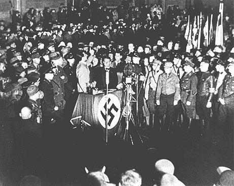 "Propaganda Minister Joseph Goebbels (at podium) praises students and members of the SA for their efforts to destroy books deemed ""un-German"" during the book burning at Berlin's Opernplatz. Germany, May 10, 1933."