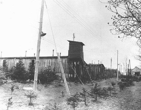 View of a watchtower and prisoner barracks at the Ohrdruf subcamp of the Buchenwald concentration camp, soon after US forces liberated Ohrdruf. Ohrdruf, Germany, April 1945.