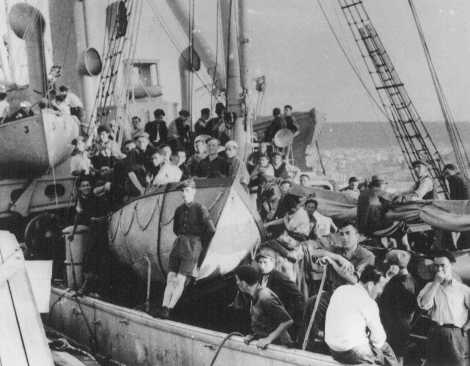 """Jewish refugees on board the Aliyah Bet (""""illegal"""" immigration) ship """"Atratto."""" The ship was caught by the British off the coast of Jaffa, Palestine, and escorted to Haifa port. July 17, 1939."""