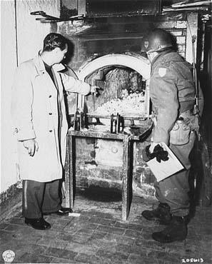 Après la libération du camp de Flossenbürg, un officier de l'armée américaine (à droite) examine un four crématoire où les victimes du camp de Flossenbürg étaient brûlées. Flossenbürg, Allemagne, 30 avril 1945.