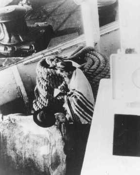 A Jewish passenger prays on board a refugee ship from Germany bound for Argentina in 1938.