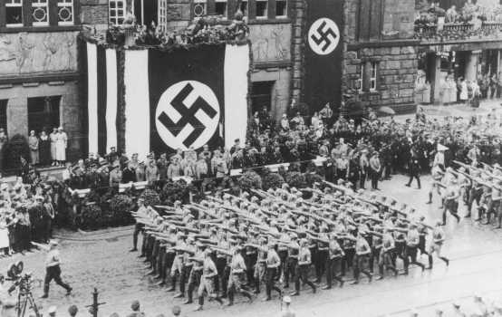 Battalions of Nazi street fighters salute Hitler during an SA parade through Dortmund. Germany, 1933.