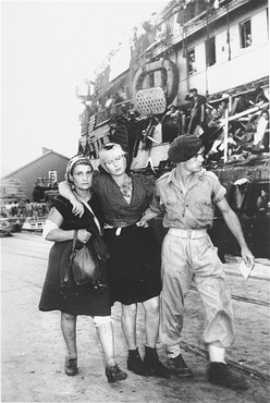 """Un soldado británico desembarca del barco """"Exodus 1947"""" a refugiados heridos mientras se resistían a los británicos. Haifa, Palestina, 20 de julio de 1947."""