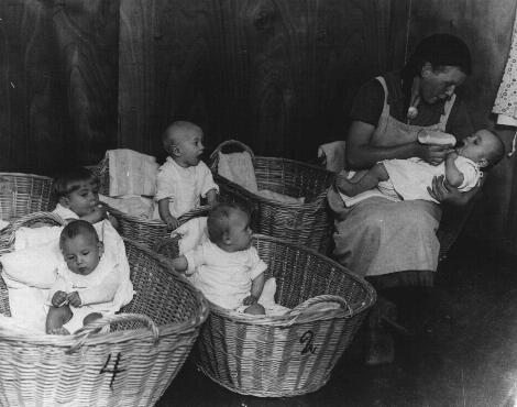 German propaganda photograph of a kindergarten for German infants promotes the nurturing role of women on the home front. Germany, 1941.