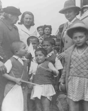 "Henrietta Szold (left, in hat), founder of the Hadassah Women's Zionist Organization, welcomes some of the Polish Jewish refugee children known as the ""Tehran Children,"" upon their arrival in Palestine. Atlit, Palestine, February 18, 1943."