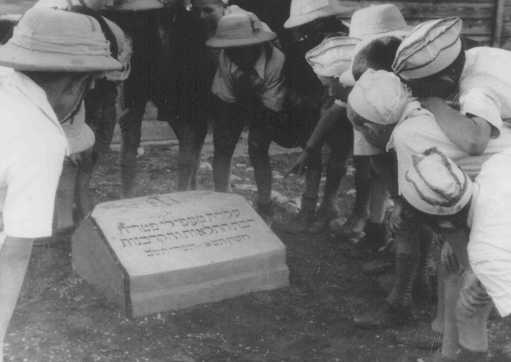 "Polish Jewish refugee children known as the ""Tehran Children"" gather at a memorial stone dedicated to the Jewish refugees who died when the ""Patria"" (a ship bound for Palestine) sank in November 1940. Atlit, Palestine, 1943."