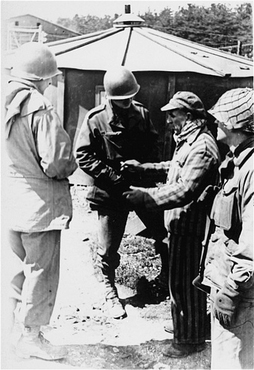A survivor of Kaufering IV, one of the Dachau subcamps in the Landsberg-Kaufering area, with American soldiers after liberation. Kaufering, Germany, after April 27, 1945.