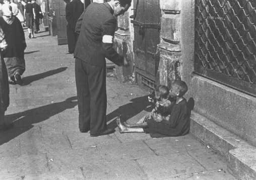 Un habitant du ghetto de Varsovie donne de l'argent à deux enfants dans une des rues du ghetto. Varsovie, Pologne, entre octobre 1940 et avril 1943.