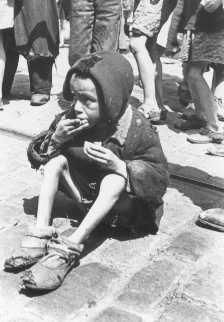 Un niño desnutrido come en las calles del ghetto de Varsovia. Varsovia, Polonia, entre 1940 y 1943.