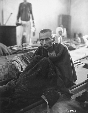 An emaciated survivor wrapped in a blanket sits up on a stretcher in the newly liberated Gusen concentration camp. Gusen, Austria, between May 5 and May 15, 1945.