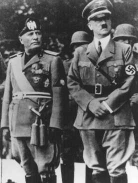 Benito Mussolini and Adolf Hitler stand together on an reviewing stand during a official visit to occupied Yugoslavia, 1941-1943.