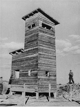 Ustasa (Croatian fascist) guard next to a watchtower at the Jasenovac concentration camp. Yugoslavia, between 1941 and 1944.