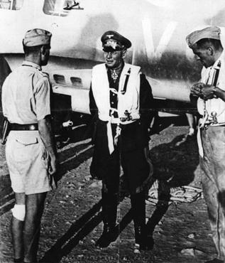 Erwin Rommel (center), commander of the Africa Corps, at an airfield in Libya during an Axis offensive into neighboring Egypt. British troops decisively defeated Rommel's forces at  El Alamein. Libya, September 8, 1942.