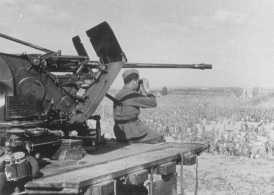 Seorang serdadu Jerman tengah menjaga tahanan perang Soviet di kamp Uman di Ukraina. Uni Soviet, 14 Agustus 1941.