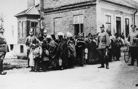German police guard a group of Roma (Gypsies) who have been rounded up for deportation to Poland. Germany, 1940-1945.