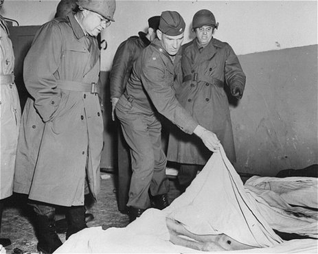 Members of a US congressional committee investigating German atrocities view the emaciated body of a dead prisoner at the Dora-Mittelbau concentration camp, near Nordhausen. Germany, May 1, 1945.