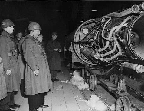 Des membres d'une commission du Congrès américain enquêtant sur les atrocités allemandes regardent une fusée V-2 sur la ligne de montage d'une usine souterraine au camp de concentration de Dora-Mittelbau, près de Nordhausen. Allemagne, 1er mai 1945.