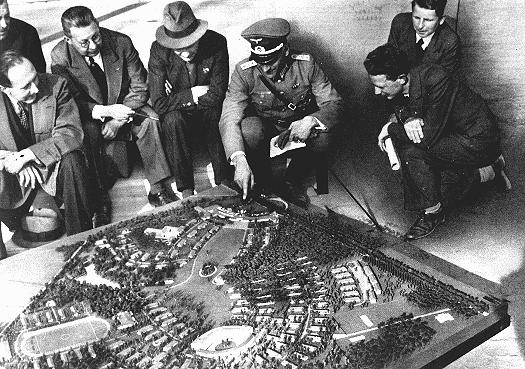 The Nazis spent lavish sums in preparation for the Olympic games. Here, German officials show the extent of the Olympic village using a scale model. Berlin, Germany, July 1936.