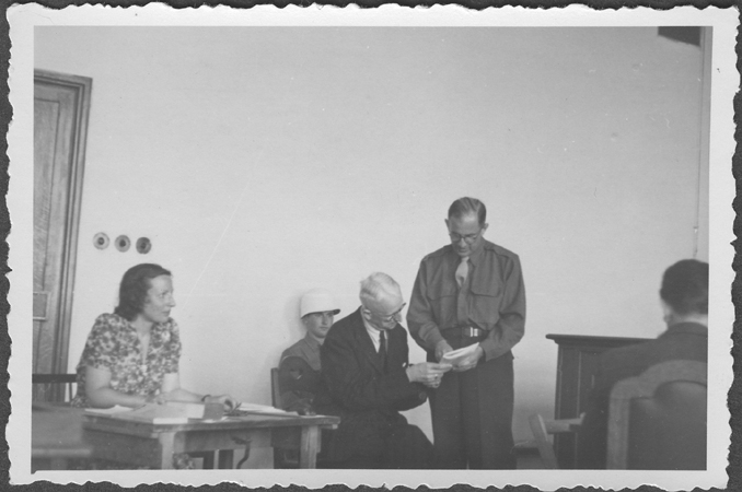 American prosecutor Robert Kempner shows a document to German Field Marshal Erich von Manstein at the IMT Nuremberg commission hearings investigating indicted Nazi organizations. Also pictured is the interpreter, a Mrs. Lowenstein. July 1946.