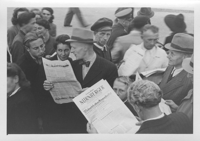 "People gather in the street to read a special edition of the ""Nurnberger"" newspaper reporting the sentences handed down by the International Military Tribunal. October 1, 1946."
