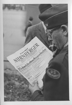 "An American correspondent reads a special edition of the ""Nurnberger"" newspaper reporting the sentences handed down by the International Military Tribunal. October 1, 1946."