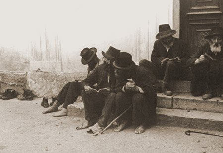 Jewish men sitting on the steps of a synagogue. Munkacs, Czechoslovakia, 1936.