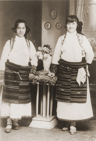 Portrait of two Jewish girls dressed in traditional Macedonian costume in a private home in Bitola. Pictured are Matilda Kamchi (or Camhi, left) and a friend. Both perished in Treblinka. Bitola, 1937.