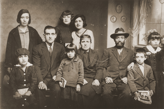 Portrait of the family of Mushon and Rebeka Kamchi in Bitola. Isak Kamchi is pictured in the front row at the right. Isak was born in Bitola. Several of his siblings and cousins left Macedonia for Palestine and North America before the war. During World War II, Isak served as the leader of a partisan unit operating in Croatia. He established a safehouse at his parent's home in Zagreb where partisans could rest and recuperate. His mother ran the safehouse, cooking for the men and nursing them back to health. When the Germans discovered the safehouse, they offered Isak protection in exchange for his surrender. However, when he did surrender, he was arrested and later killed. He may have been publicly hanged. Photograph taken in Bitola, ca. 1932.