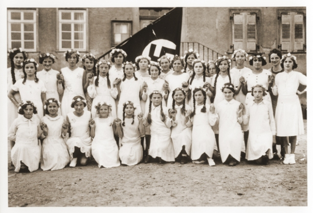 Group portrait of German girls posing outside their school in front of a Nazi flag. Among those pictured is Lilli Eckstein six months before she was expelled from the school for being Jewish. Heldenbergen, Germany, 1935.