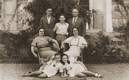 Members of the Amarillo family pose outside their home in Salonika. Front, from left to right, are Tillie Amarillo and Sarika Yahiel. Seated behind them are their mothers Louisa Bourla Amarillo and Regina Amarillo Yahiel. Standing are Saul Amarillo, Isaccino Yahiel, and Isaac Yahiel. Salonika, Greece, between 1930 and 1939.