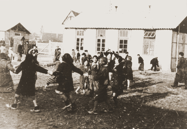 Romani (Gypsy) children play outside at the Jargeau internment camp. The camp was established in response to a German order in October 1940 calling for the arrest and confinement in camps of all Frenchmen or foreigners in the Loiret region who did not have a permanent residence. Jargeau, France, 1941-1945.