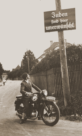 "A motorcyclist reads a sign stating ""Jews are not welcomed here."" Germany, ca. 1935."