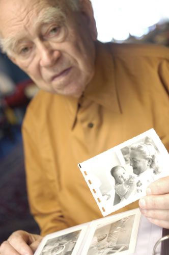 Norman Salsitz holds a photograph of his wife, Amalie, and daughter, Esther. 2004.